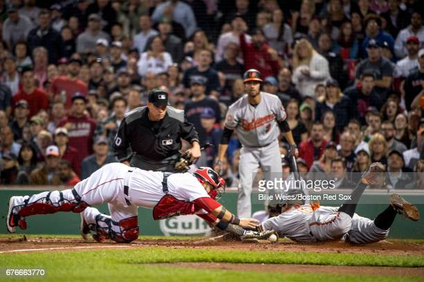 Jonathan Schoop of the Baltimore Orioles slides as he evades the tag of Sandy Leon of the Boston Red Sox to score during the fifth inning of a game...