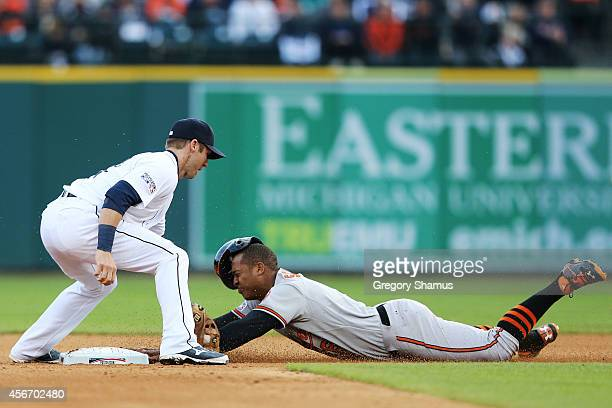 Jonathan Schoop of the Baltimore Orioles steals second base as Andrew Romine of the Detroit Tigers attempts to make the tag in the seventh inning...