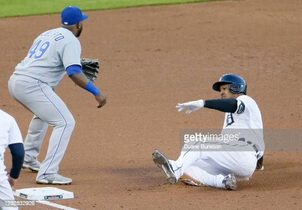 Jonathan Schoop of the Detroit Tigers slides into third base for a triple as third baseman Hanser Alberto of the Kansas City Royals covers the bag...
