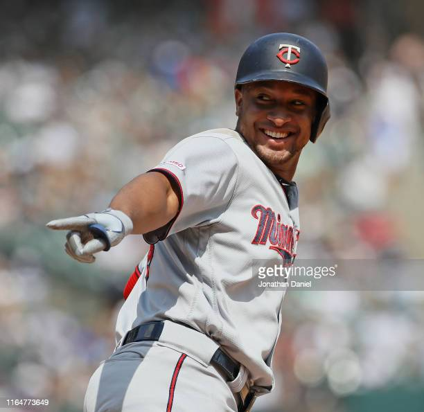 Jonathan Schoop of the Minnesota Twins smiles and points to the dugout as he runs the bases after hitting a two run home run in the 5th inning...