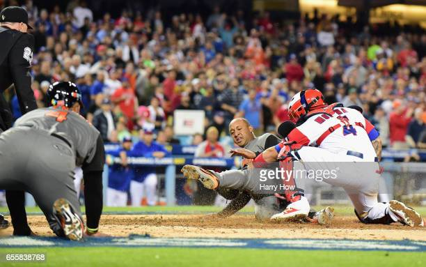 Jonathan Schoop of the Netherlands slides into home as catcher Yadier Molina of the Puerto Rico tags him out in the fifth inning during Game 1 of the...