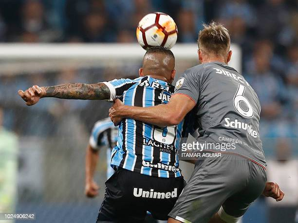 Jonathan Schunke of Argentina's Estudiantes vies for the ball with Jael of Brazil's Gremio during their Copa Libertadores 2018 football match held at...