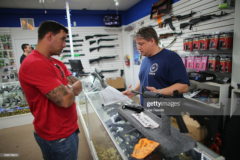 Jonathan Schwartz (R), a salesman at the National Armory gun store, fills out the paperwork for Reese Magnant as he buys a National Armory AR-15 Battle Entry Assault Rife on January 16, 2013 in Pompano Beach, Florida. President Barack Obama today in Washington, DC announced a broad range of gun initiatives that his administration thinks will help curb gun violence.