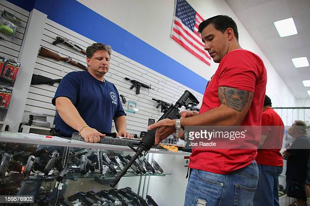Jonathan Schwartz a salesman at the National Armory gun store helps Reese Magnant as he looks to buy a National Armory AR15 Battle Entry Assault...