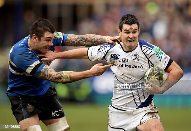 Jonathan Sexton of Leinster holds off Ryan Caldwell of Bath during the Heineken Cup match between Bath Rugby and Leinster at Recreation Ground on...