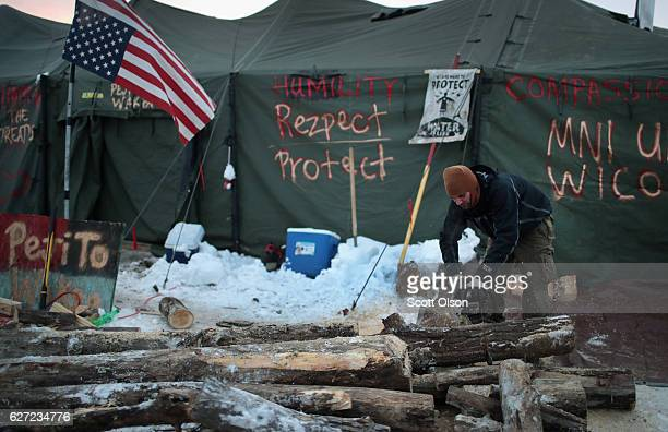 Jonathan Shields from Portland, Oregon helps to cut firewood in front of the Cheyenne River Sioux Tribe tent at Oceti Sakowin Camp on the edge of the...