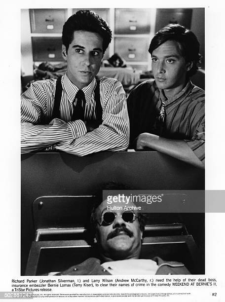Jonathan Silverman and Andrew McCarthy look to help their dead boss Terry Kiser in a scene from the TriStar Pictures movie Weekend at Bernie's II...
