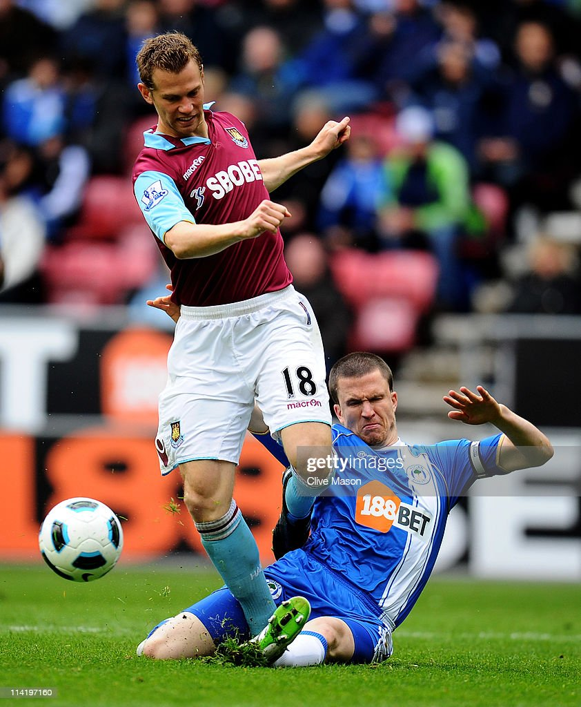 Jonathan Spector of West Ham United is tackled by Gary Caldwell of Wigan Athletic during the Barclays Premier League match between Wigan Athletic and West Ham United at the DW Stadium on May 15, 2011 in Wigan, England.
