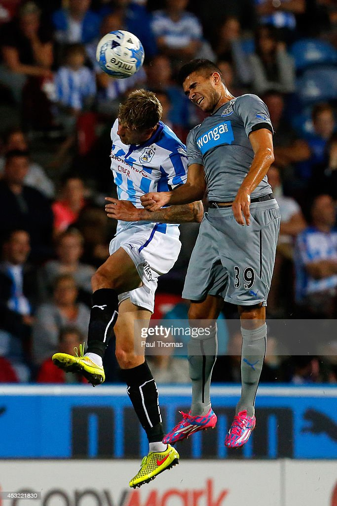 Jonathan Stead (L) of Huddersfield in action with Mehdi Abeid of Newcastle during the Pre Season Friendly match between Huddersfield Town and Newcastle United at the John Smith's Stadium on August 5, 2014 in Huddersfield, England.