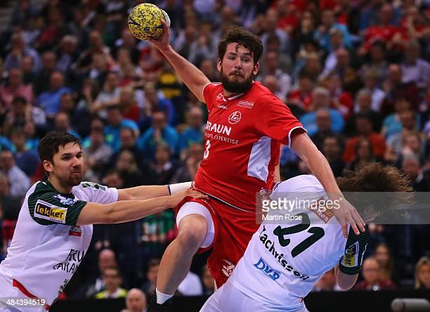 Jonathan Stenbaecken of Melsungen challenges for the ball with Mattias Zachrisson and Fabian Wieder of Berlin during the DHB Pokal handball semi...