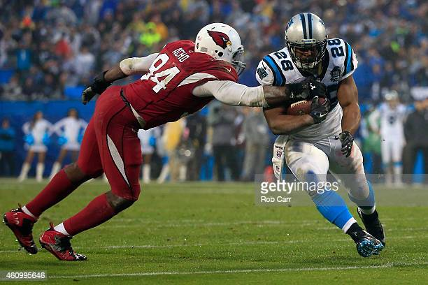 Jonathan Stewart of the Carolina Panthers breaks a tackle from Sam Acho of the Arizona Cardinals during their NFC Wild Card Playoff game at Bank of...