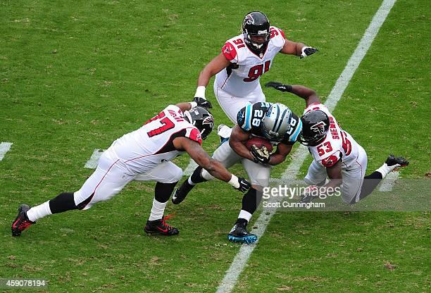 Jonathan Stewart of the Carolina Panthers carries the ball against Ra'Shede Hageman and Prince Shembo of the Atlanta Falcons at Bank Of America...