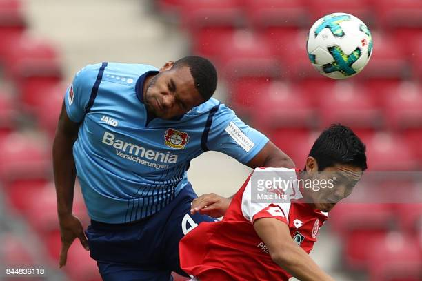Jonathan Tah of Bayer Leverkusen fights for then ball with Yoshinori Muto of Mainz during the Bundesliga match between 1 FSV Mainz 05 and Bayer 04...