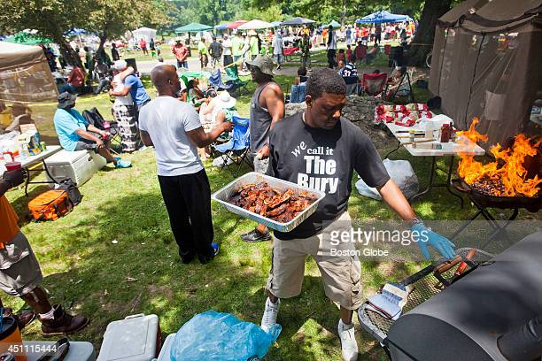 Jonathan Talley, of Roxbury, grills chicken, ribs, and sausage at Franklin Park for the Juneteenth celebration on Saturday afternoon, June 21, 2014....