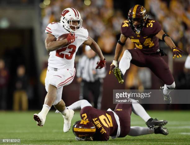 Jonathan Taylor of the Wisconsin Badgers carries the ball for a touchdown after avoiding a tackle by Jacob Huff and Antonio Shenault of the Minnesota...