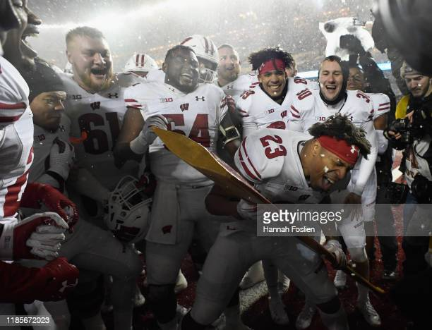 Jonathan Taylor of the Wisconsin Badgers celebrates defeating the Minnesota Golden Gophers by using the Paul Bunyan Axe trophy after the game at TCF...
