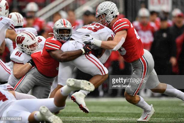 Jonathan Taylor of the Wisconsin Badgers is brought down by Baron Browning and Pete Werner of the Ohio State Buckeyes after a short gain in the...