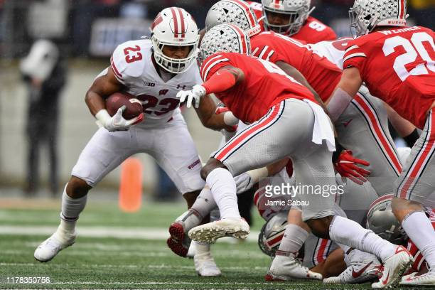 Jonathan Taylor of the Wisconsin Badgers looks for running room as Jordan Fuller of the Ohio State Buckeyes closes in during the second quarter at...