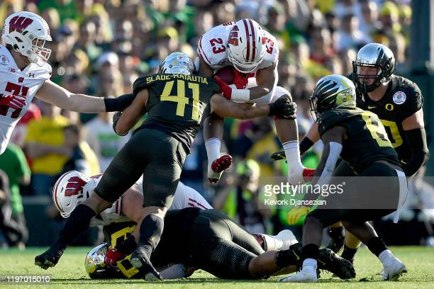 Jonathan Taylor of the Wisconsin Badgers runs the ball for a 5 yard gain and gets tackled by Isaac SladeMatautia of the Oregon Ducks during the first...