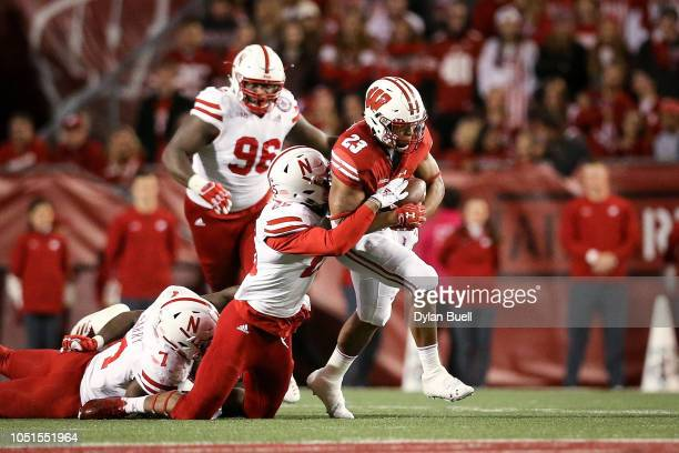 Jonathan Taylor of the Wisconsin Badgers runs with the ball while being tackled by Antonio Reed of the Nebraska Cornhuskers in the third quarter at...