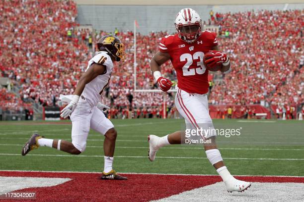 Jonathan Taylor of the Wisconsin Badgers scores a touchdown past Norman Anderson of the Central Michigan Chippewas in the first quarter at Camp...
