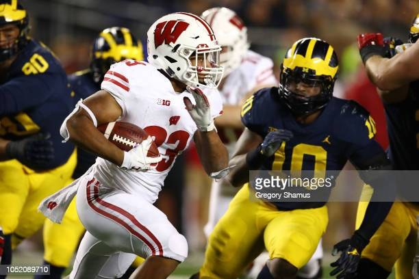 Jonathan Taylor of the Wisconsin Badgers tries to outrun the tackle of Devin Bush of the Michigan Wolverines during the second half on October 13...