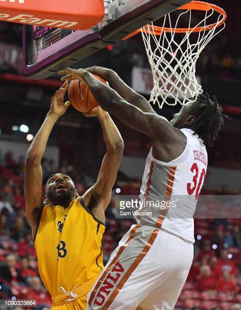 Jonathan Tchamwa Tchatchoua of the UNLV Rebels blocks a shot from Trevon Taylor of the Wyoming Cowboys during their game at the Thomas Mack Center on...
