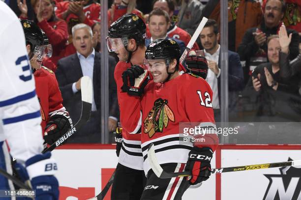 Jonathan Toews and Alex DeBrincat of the Chicago Blackhawks celebrate after Toews scored against the Toronto Maple Leafs in the first period at the...