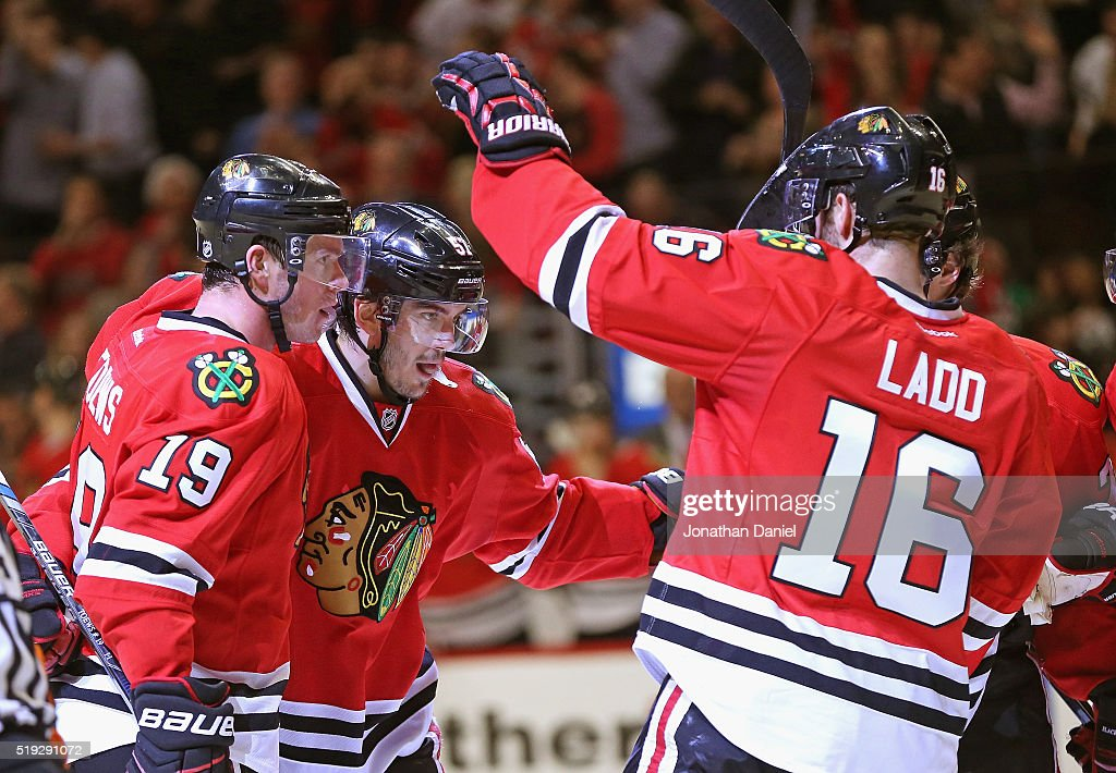 Jonathan Toews #19 and Andrew Ladd #16 of the Chicago Blackhawks celebrate a second period goal by Trevor van Riemsdyk #57 (center) against the Arizona Coyotes at the United Center on April 5, 2016 in Chicago, Illinois.