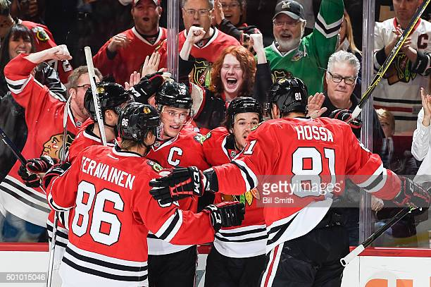 Jonathan Toews and Andrew Shaw of the Chicago Blackhawks celebrate with teammates after Toews scored against the Winnipeg Jets in the first period of...