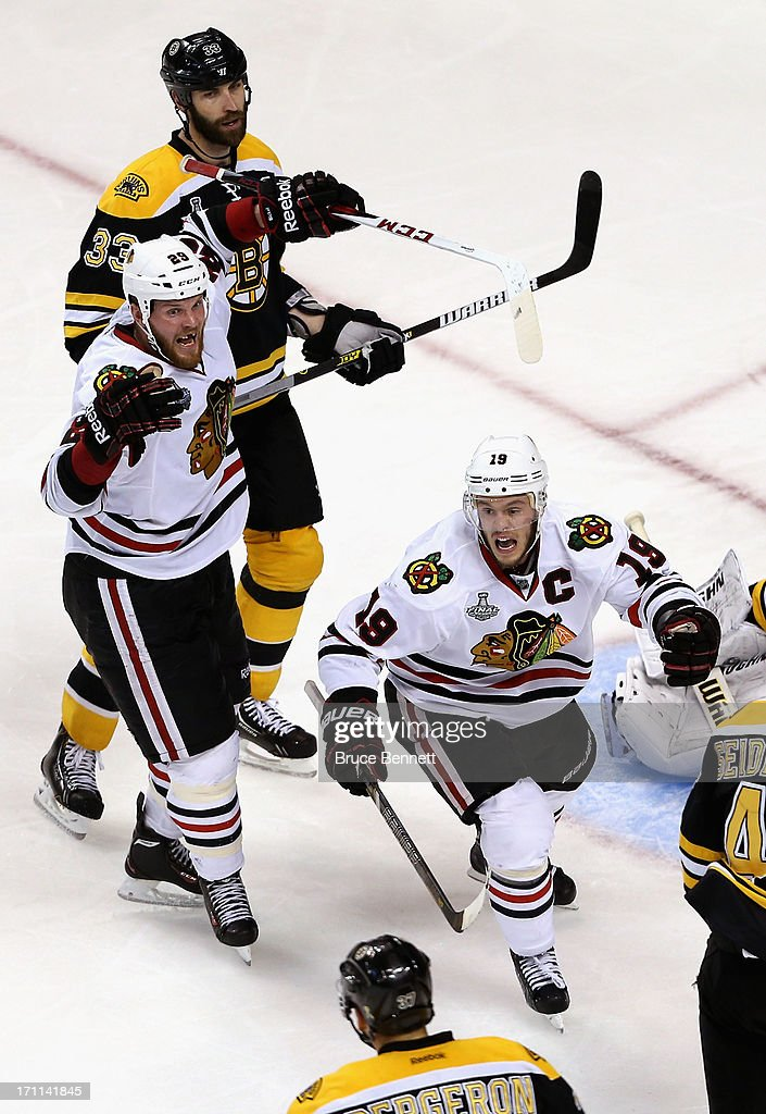 Jonathan Toews #19 and Bryan Bickell #29 of the Chicago Blackhawks celebrate after Brent Seabrook #7 scored the game-winning goal in overtime to give them a 6-5 win against Zdeno Chara #33 of the Boston Bruins in Game Four of the 2013 NHL Stanley Cup Final at TD Garden on June 19, 2013 in Boston, Massachusetts.