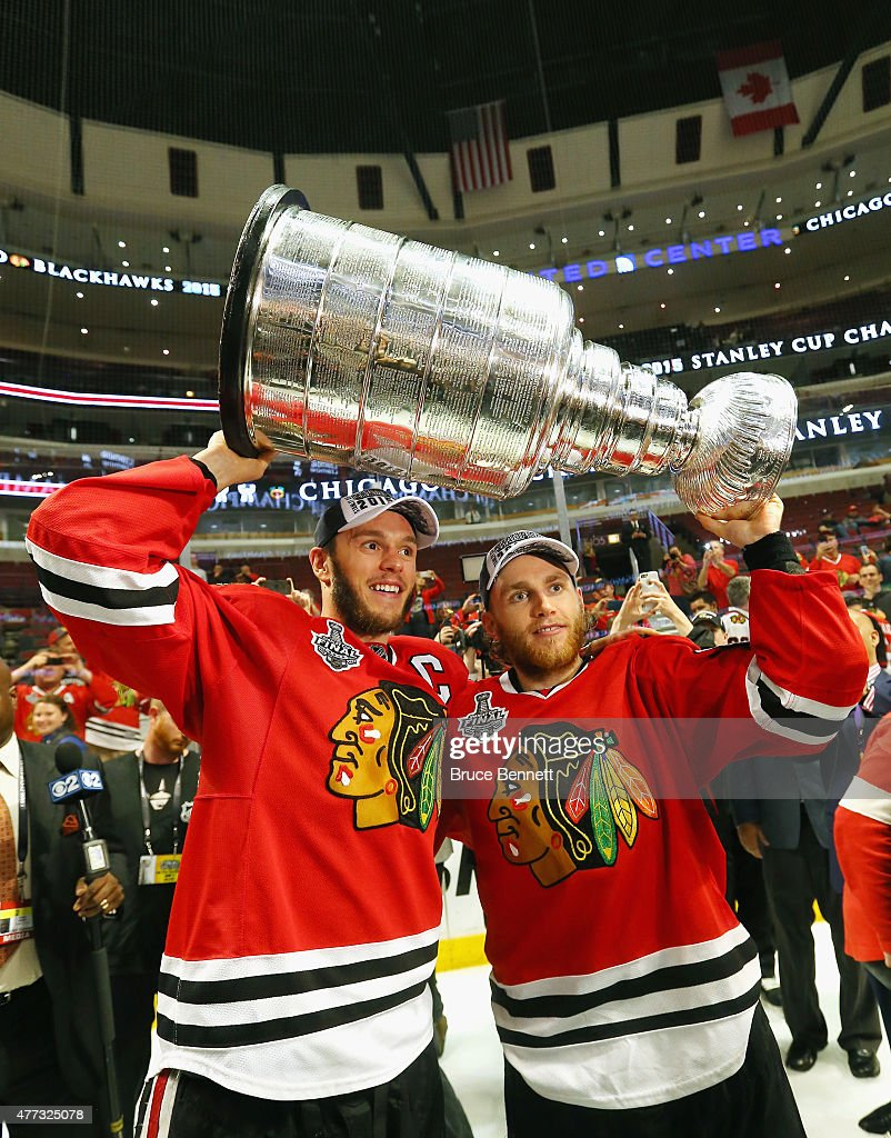 Jonathan Toews #19 and Patrick Kane #88 of the Chicago Blackhawks celebrate by hoisting the Stanley Cup after defeating the Tampa Bay Lightning by a score of 2-0 in Game Six to win the 2015 NHL Stanley Cup Final at the United Center on June 15, 2015 in Chicago, Illinois.