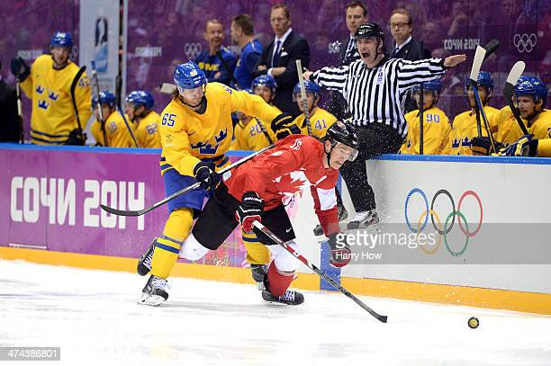 Jonathan Toews of Canada falls to the ice while competing with Erik Karlsson of Sweden for the puck during the Men's Ice Hockey Gold Medal match on...