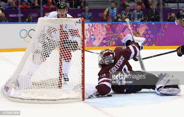 Jonathan Toews of Canada watches as Kristers Gudlevskis of Latvia tries to stop a puck during the Men's Ice Hockey Quarterfinal Playoff on Day 12 of...