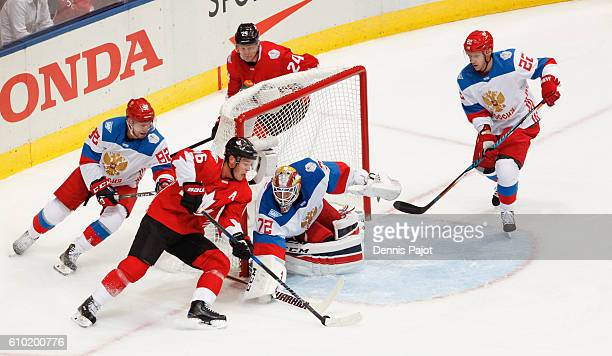 Jonathan Toews of Team Canda is poke checked by Sergei Bobrovsky of Team Russia while attempting a wrap around with Evgeny Kuznetsov following close...