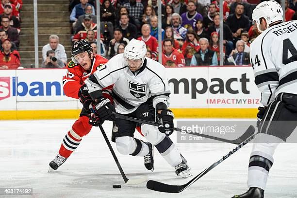 Jonathan Toews of the Chicago Blackhawks and Andrej Sekera of the Los Angeles Kings chase the puck during the NHL game at the United Center on March...