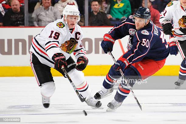 Jonathan Toews of the Chicago Blackhawks and Antoine Vermette of the Columbus Blue Jackets chase down a loose puck during the third period on October...