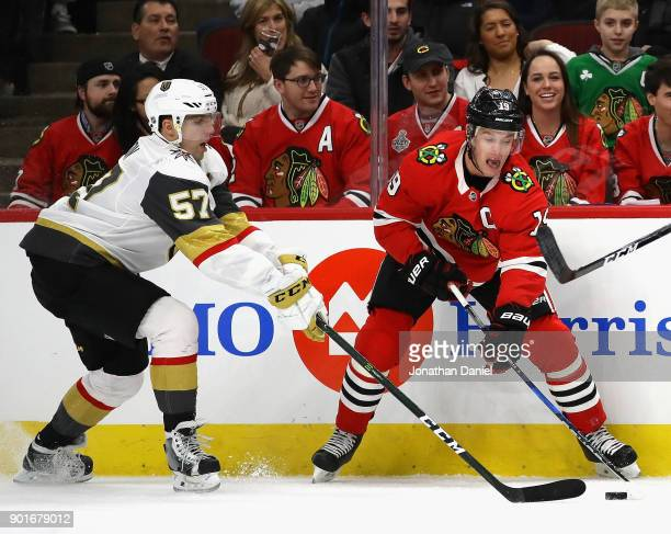 Jonathan Toews of the Chicago Blackhawks and David Perron of the Vegas Golden Knights battle for the puck along the boards at the United Center on...