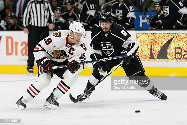 Jonathan Toews of the Chicago Blackhawks and Drew Doughty of the Los Angeles Kings skate to the puck during a game at Staples Center on November 28...