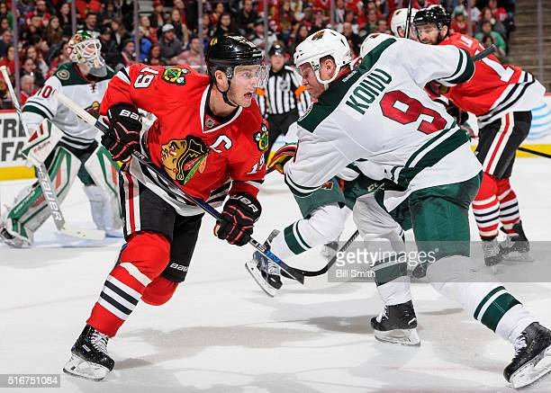 Jonathan Toews of the Chicago Blackhawks and Jarret Stoll of the Minnesota Wild skate in the second period of the NHL game at the United Center on...