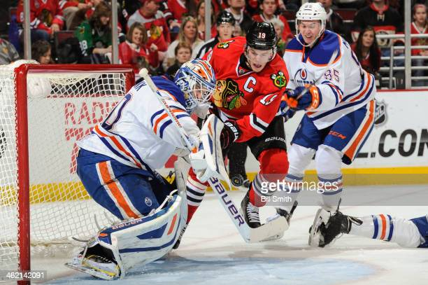 Jonathan Toews of the Chicago Blackhawks and Martin Marincin of the Edmonton Oilers charge toward the puck as goalie Devan Dubnyk of the Edmonton...