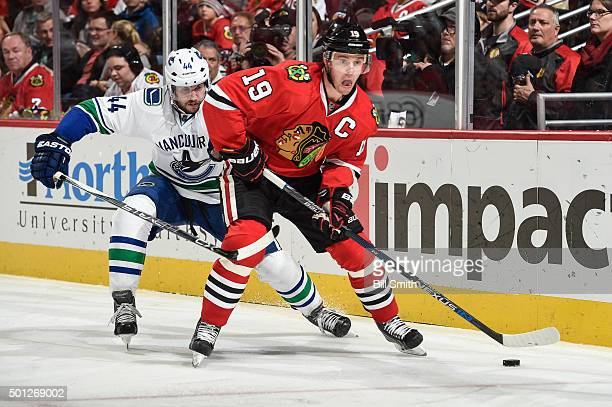 Jonathan Toews of the Chicago Blackhawks and Matt Bartkowski of the Vancouver Canucks chase the puck during the NHL game at the United Center on...