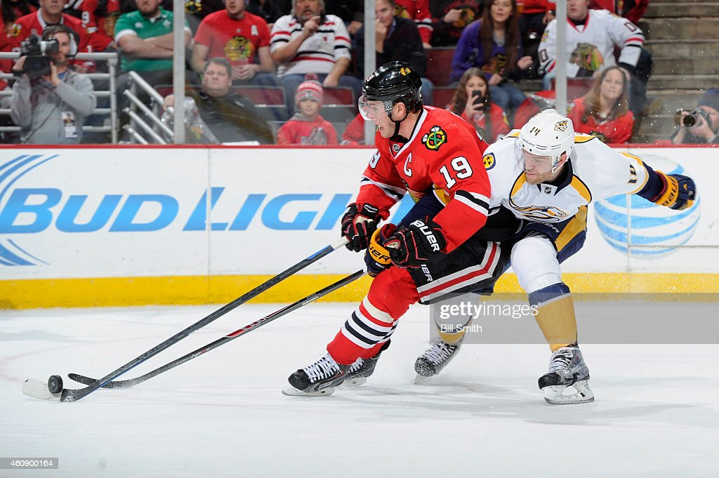 Jonathan Toews #19 of the Chicago Blackhawks and Mattias Ekholm #14 of the Nashville Predators chase the puck during the NHL game at the United Center on December 29, 2014 in Chicago, Illinois.