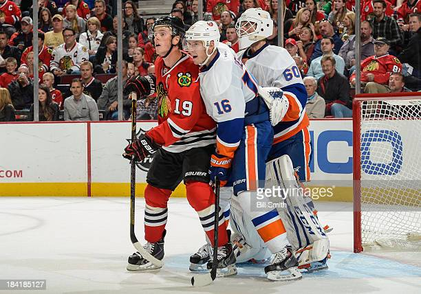 Jonathan Toews of the Chicago Blackhawks and Peter Regin of the New York Islanders stand in position in front of Islanders goalie Kevin Poulin during...