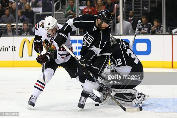 Jonathan Toews of the Chicago Blackhawks and Rob Scuderi of the Los Angeles Kings look for the rebound near the crease area in the first period of...