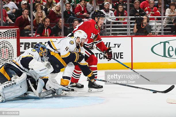 Jonathan Toews of the Chicago Blackhawks and Ryan Ellis of the Nashville Predators reach for the puck in front of goalie Marek Mazanec in the second...