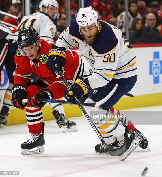 Jonathan Toews of the Chicago Blackhawks and Ryan O'Reilly of the Buffalo Sabres battle at the United Center on December 8 2017 in Chicago Illinois...