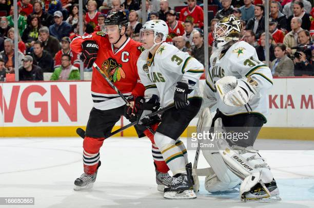 Jonathan Toews of the Chicago Blackhawks and Stephane Robidas of the Dallas Stars stand in position in front of goalie Richard Bachman of the Stars...