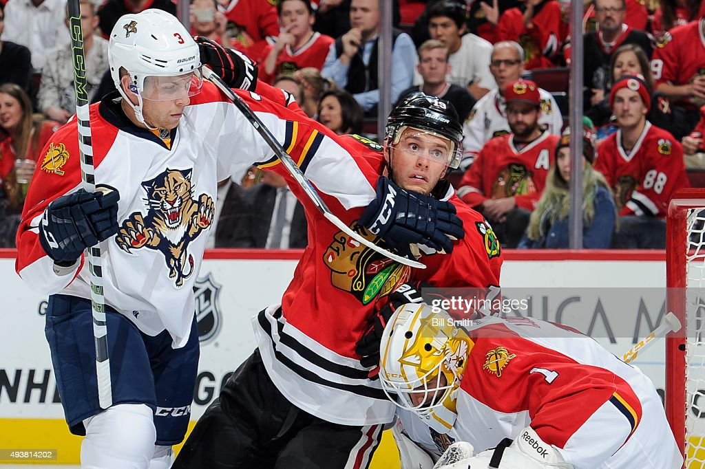 Jonathan Toews #19 of the Chicago Blackhawks and Steven Kampfer #3 of the Florida Panthers watch for the puck next to goalie Roberto Luongo #1 in the first period of the NHL game at the United Center on October 22, 2015 in Chicago, Illinois.