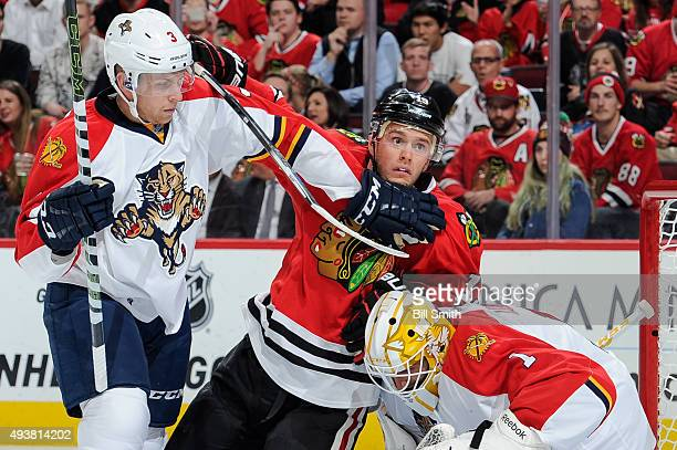 Jonathan Toews of the Chicago Blackhawks and Steven Kampfer of the Florida Panthers watch for the puck next to goalie Roberto Luongo in the first...
